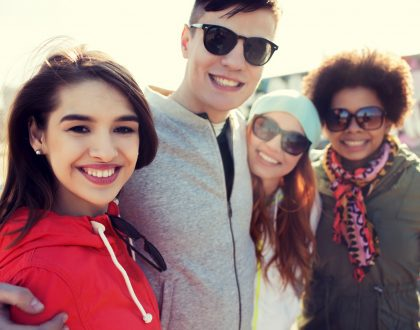 happy teenage friends in shades hugging outdoors