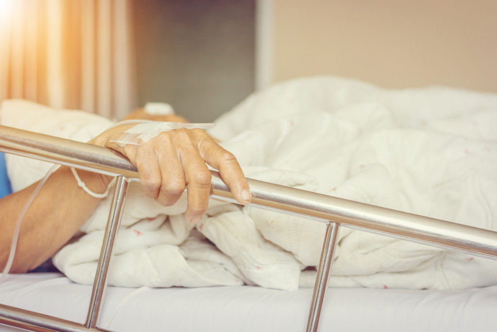 Close up of Asian elderly women patient's hand on a drip receiving a saline solution holding on to the bed in hospital