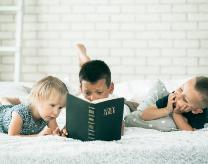 children read a bible on the bed