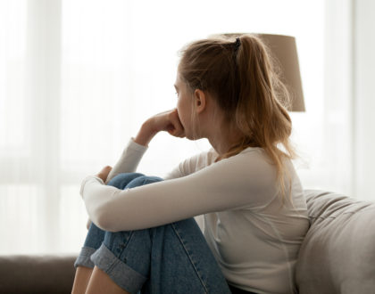 Upset woman sitting on couch alone at home