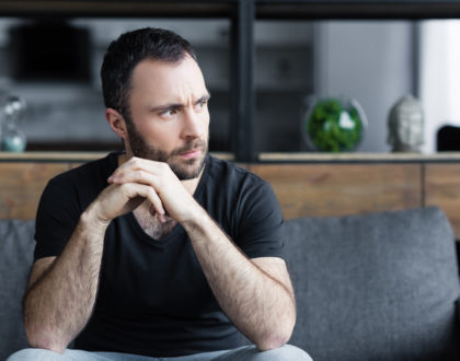 serious bearded man sitting on sofa with folded hands and looking away