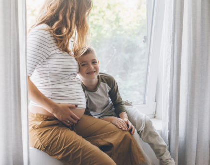 Pregnant mom playing with child in bedroom