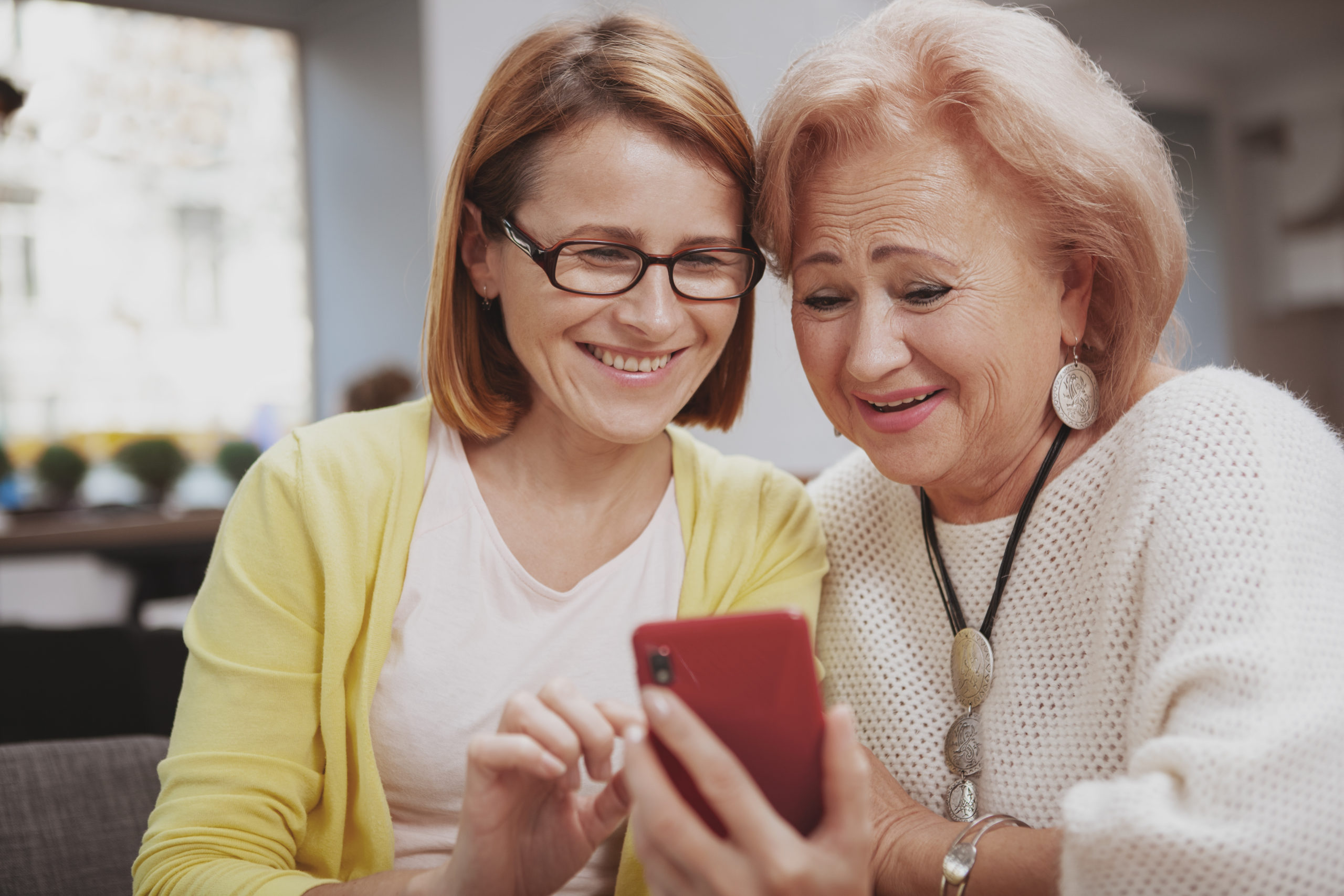 Close up of happy senior mother and her mid aged daughter using smart phone together, copy space