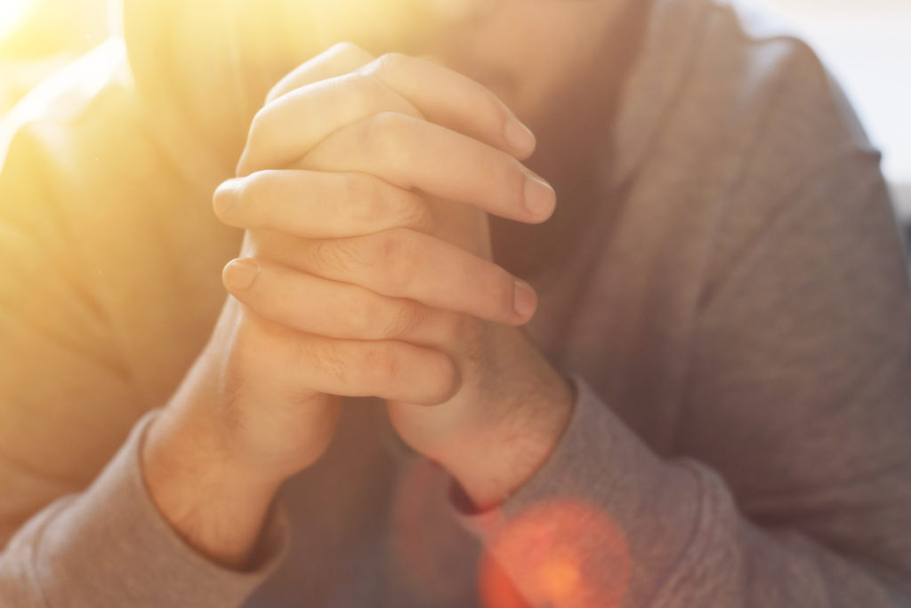 Bearded adult man praying to God sitting at home in the sunbeam. A Muslim or Christian raises his hands to God. Crossed hands in prayer gesture close up