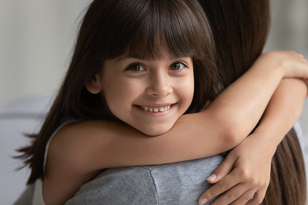 Portrait of smiling girl hug cuddle with young mom