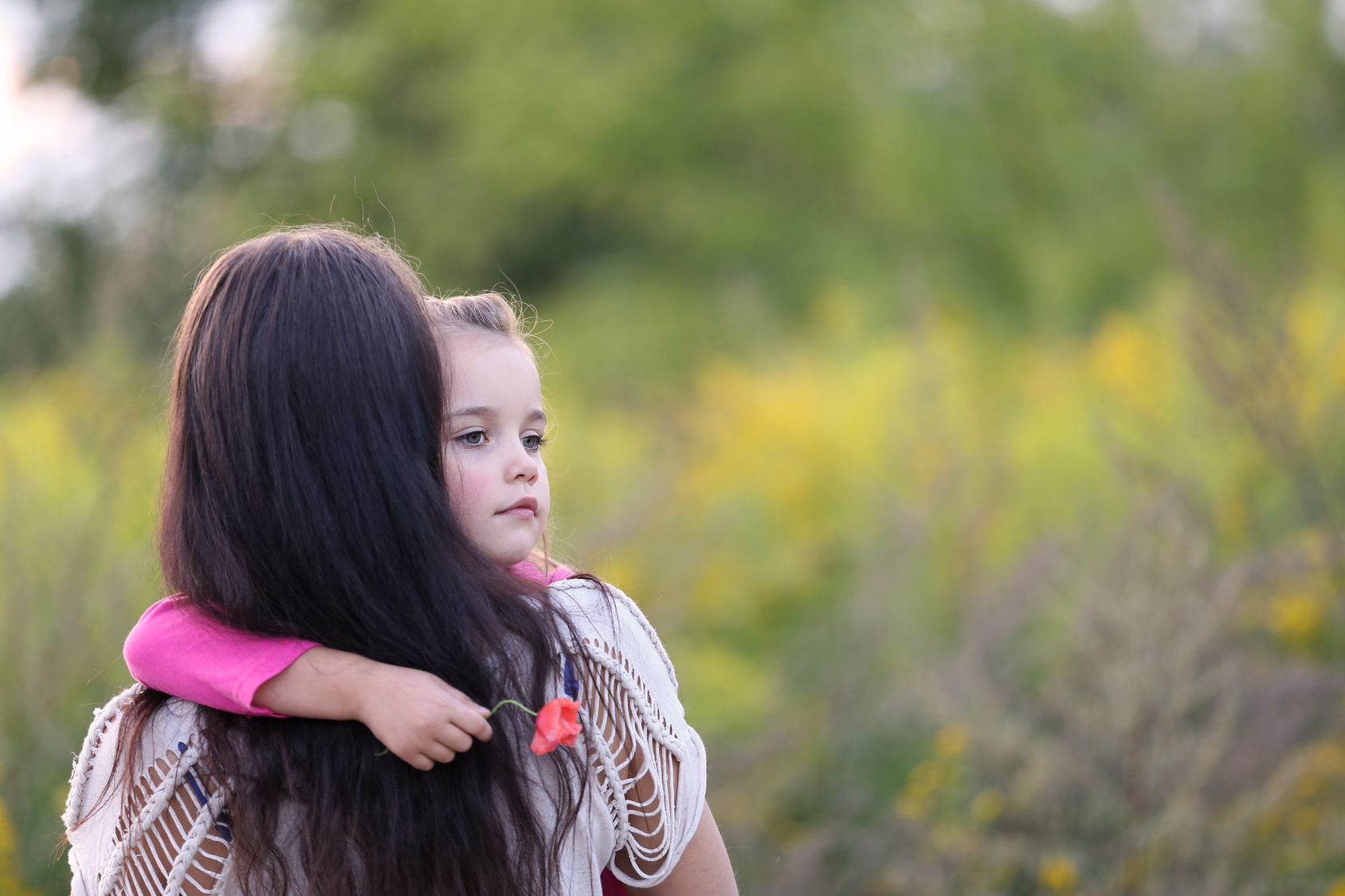 very sad little girl in her mother's arms