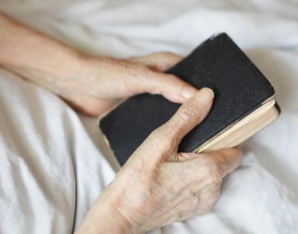 Praying hands of a senior woman at home with Bible.