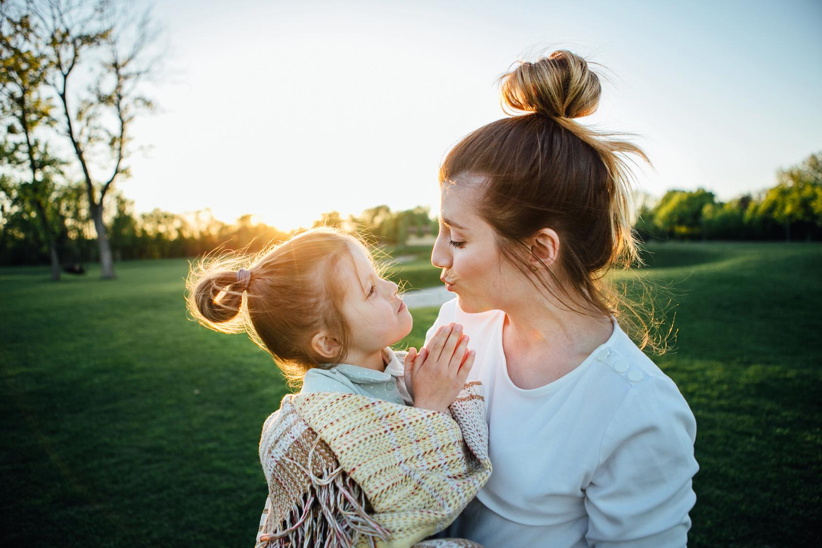 Mother hugs her daughter.