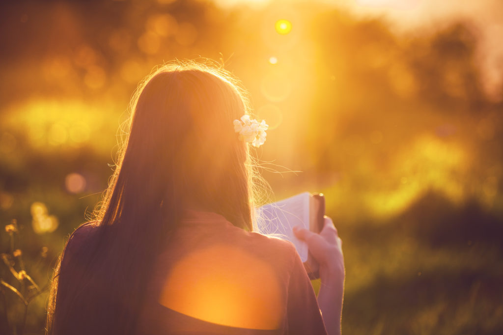 Girl reading the Bible at sunset