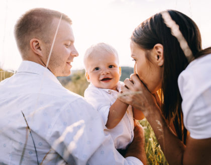 Walk beautiful young family in white clothes with a young son blond in mountainous areas with tall grass at sunset. Parents from both sides embracing son, hugging. family - this is happiness