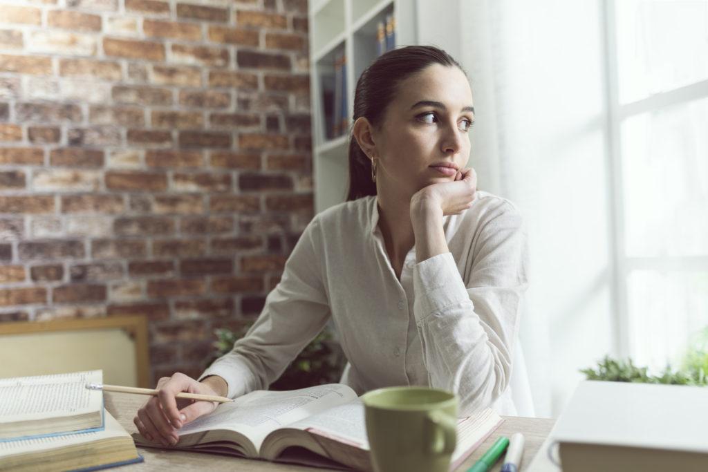 Pensive student doing homework at home