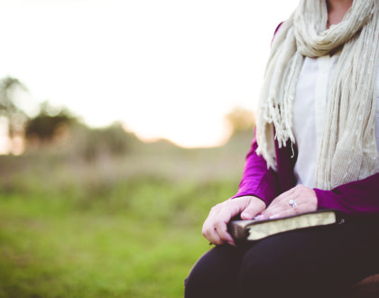 Closeup shot of a female sitting while holding the bible with a blurred background