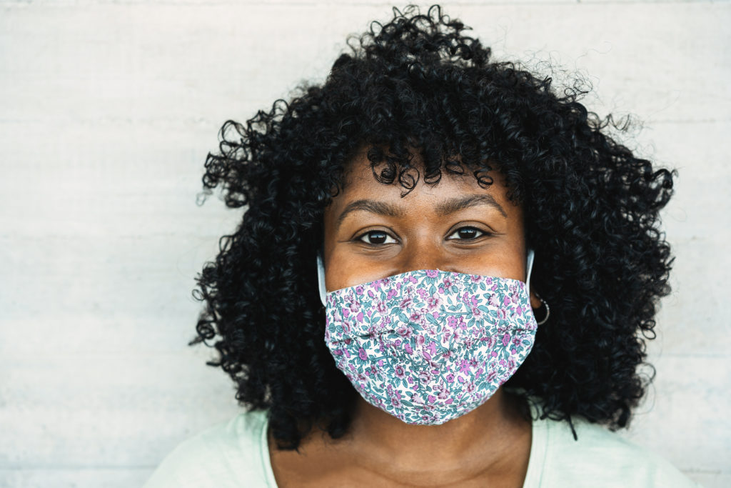 Happy black girl smiling under protective face mask - Young millennial person during coronavirus lifestyle - Health care and happiness concept - Focus on face