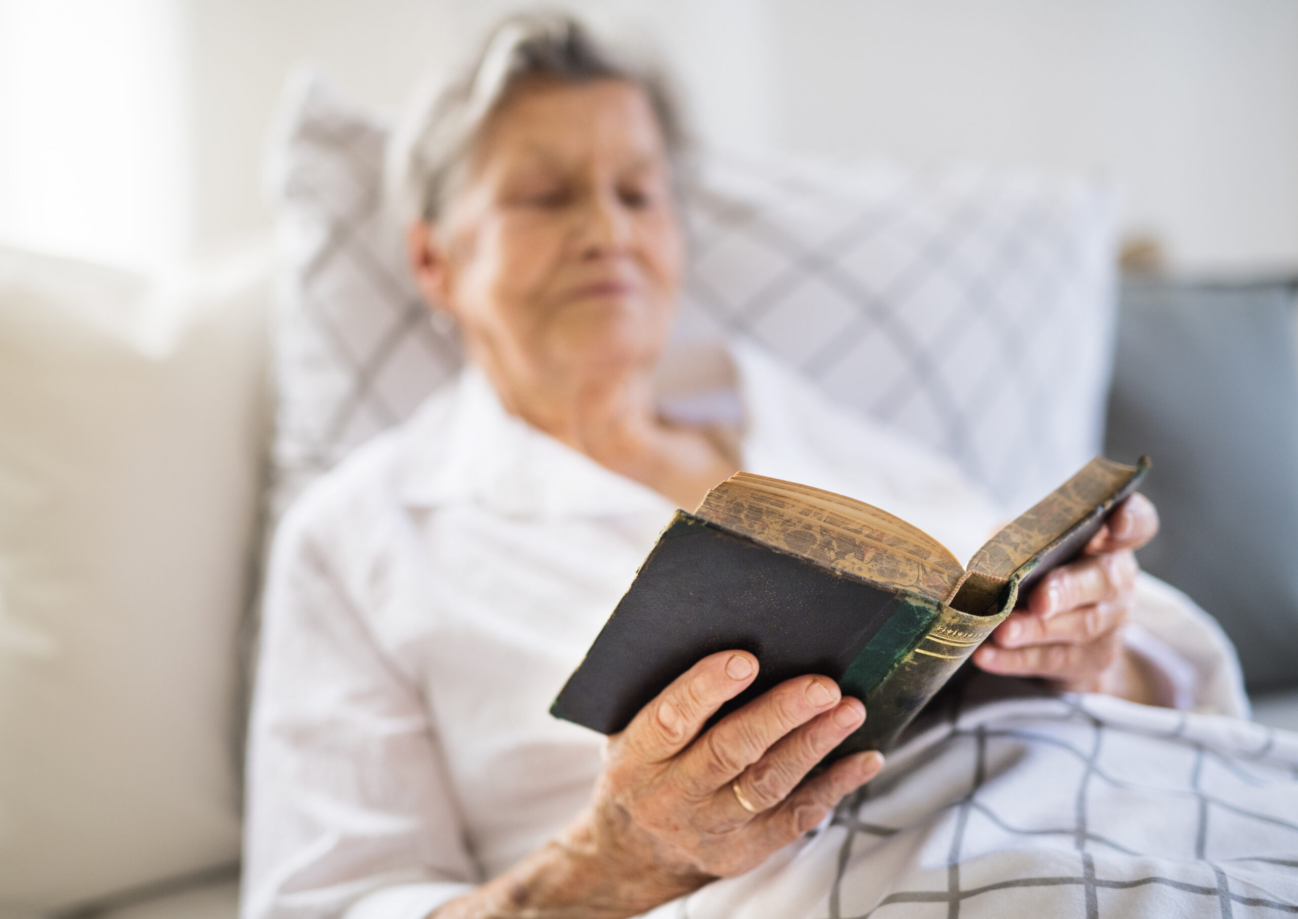 Sick senior woman reading bible book in bed at home or in hospital.