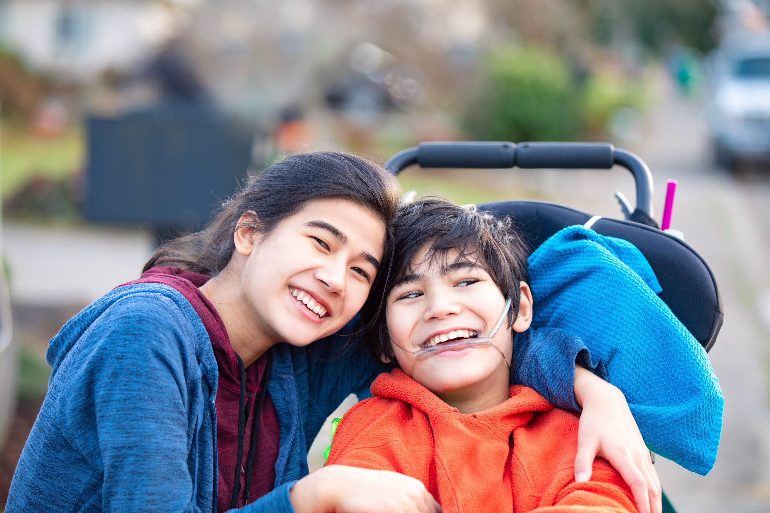 Big sister hugging disabled brother in wheelchair outdoors, smiling