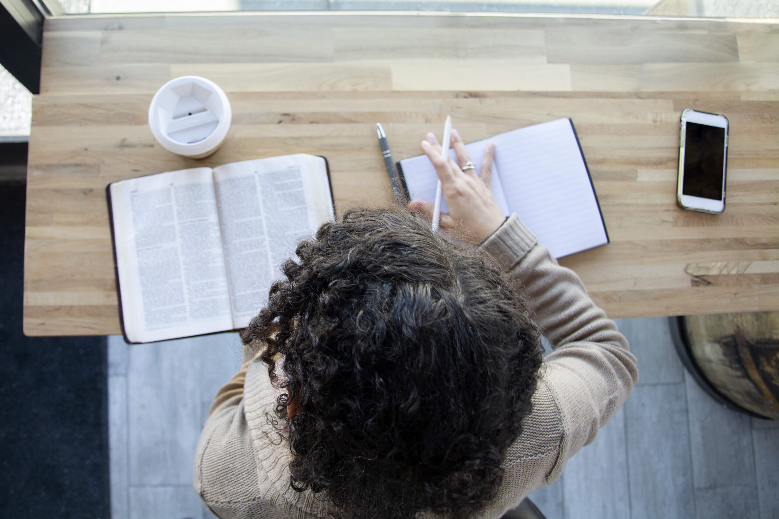 top view of black woman making notes while studying her bible