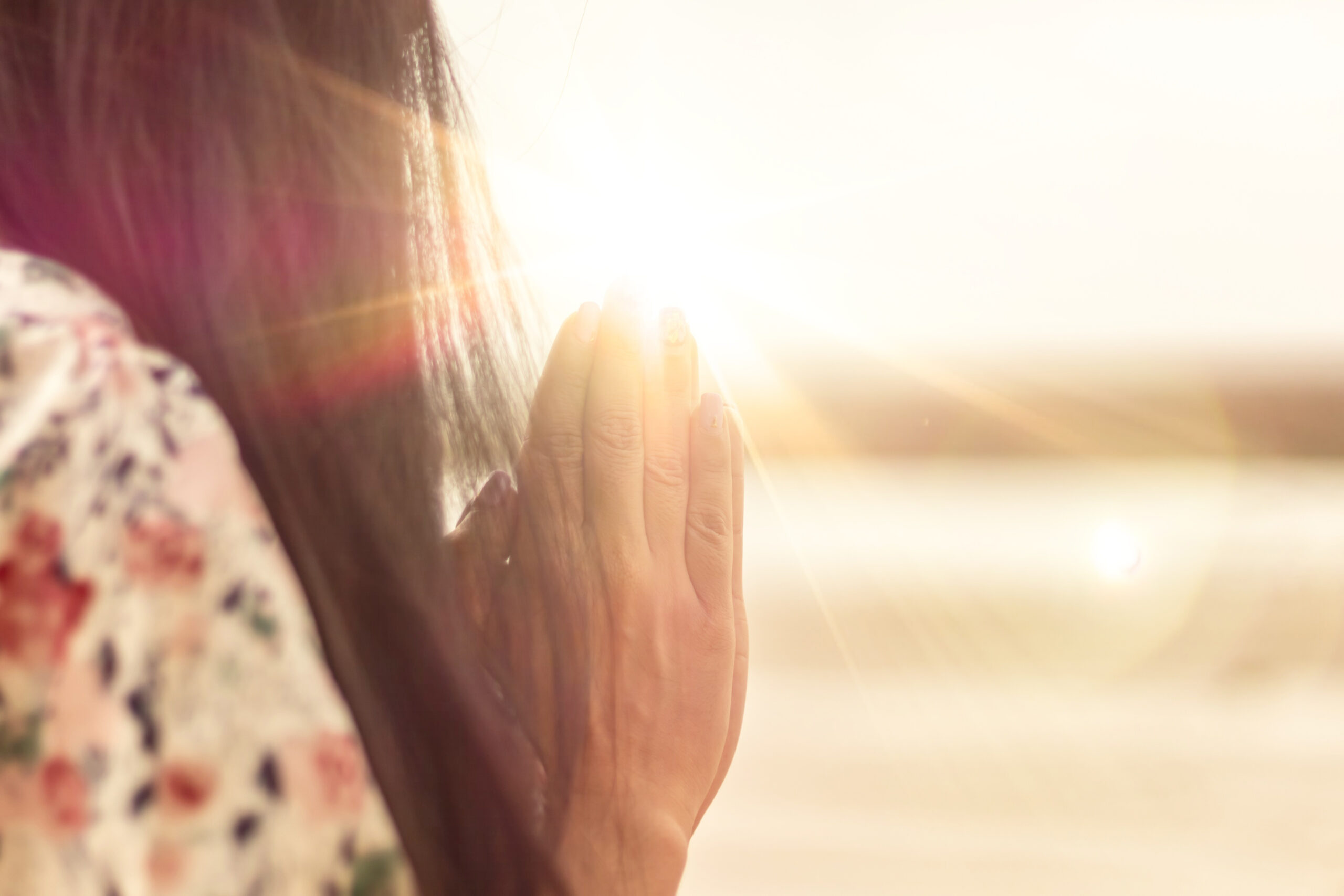 A woman praying hand for blessings When the sun goes down Hope for a happy life