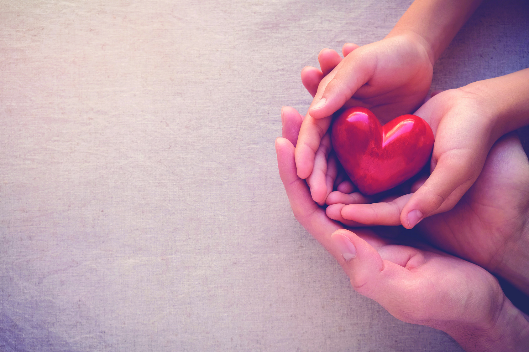 adult and child hands holding red heart, health care love
